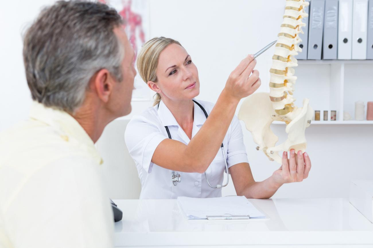 doctor-showing-her-patient-a-spine-model