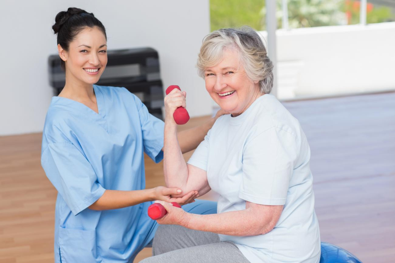 instructor-assisting-senior-woman-in-lifting-dumbbells