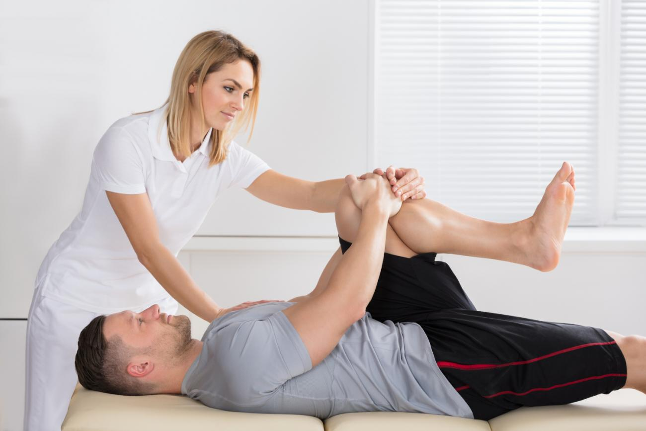 physiotherapist-giving-knee-exercise-to-a-man